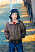 Boy homeless bum in brown jacket and a fur hat and crumpled jean — Stock Photo
