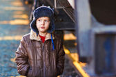 Boy homeless bum on street freezing close to railway carriage in — Stock Photo