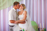 Bride and groom kissing newlyweds room at a banquet in the hall — Stock Photo