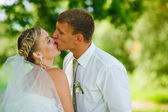 Bride and groom newlyweds kissing in the woods on a green backgr — Stock Photo