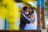 Bride and groom standing at old wooden house and kiss around yel — Stock Photo