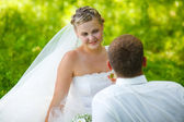 Bride looking at groom wedding couple on a green background — Stock Photo