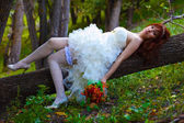 Bride red haired woman in a white dress with sexy legs with gart — Stock Photo