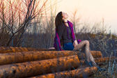 Brunette girl sitting woman outside in a group timber planks aut — Stock Photo