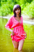 Brunette woman in red dress wet to the waist in the water touche — Stock Photo