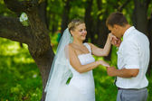 Groom kissing hand of bride, newlyweds couple are in a green for — Stock Photo