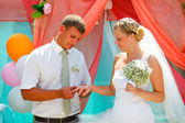 Groom wears the ring bride at a wedding couple newlyweds registr — Stock Photo