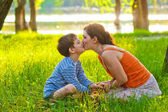 Mom and son of woman and child sitting on grass kissing at sunse — Stock Photo