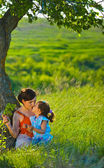 Mother, daughter, woman and child sitting in the green grass nea — Stock Photo