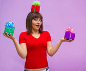 Surprised woman with open mouth holds a box with gifts on his he — Stock Photo