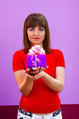 Woman in red shirt holding a gift box with a purple ribbon on pu — Stock Photo