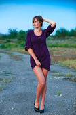 Young woman knitted dress of purple on blue background with natu — Stock Photo