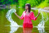 Brunetka dama czerwona sukienka jest mokry do pasa w plusk wody dotyka — Zdjęcie stockowe