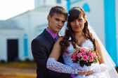 Couple man and woman at wedding next to church on blue backgroun — Stock Photo