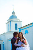 Couple man and woman wedding next church on blue background on s — Stock Photo