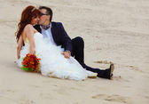 Newly married couple are on beach, bride sit and groom are kissi — Stock Photo