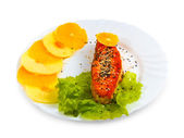 Fried fish salmon with orange and apple leaf lettuce on plate is — Stock Photo