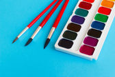 Brushes for watercolors paints children on blue background — Stock Photo