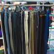 Different group colored jeans hanging on a hanger in store — Stock Photo
