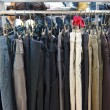 Group different colored jeans hanging on a hanger in store — Stock Photo #16273933