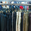 Group of different colored jeans hanging on a hanger in store — Stock Photo