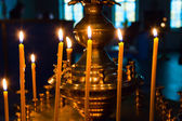 Lighting fire candles in russian orthodox church — Stock Photo