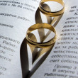 Wedding ring on a book with a shadow in the shape of a heart — Stock Photo