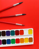 Watercolor paints and brushes on the red texture art palette — Stock Photo