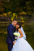 Bride and groom standing at the water behind the yellow leaves f — Stock Photo