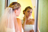 Portrait bride standing in front of a mirror corrects earring we — Stock Photo