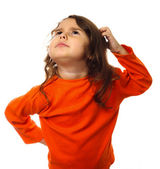 Portrait brunette kid in orange sweater, scratching his head thi — Stock Photo