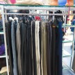 Stock Photo: Shop pants different group colored jeans hanging on hanger in
