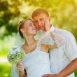 Sunlight bride blonde groom newlyweds standing in a green forest - Stockfoto