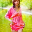 Sunlight brunette woman in red dress wet to the waist in the wat — Stock Photo