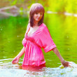 Sunlight brunette woman red dress is wet to waist in water touch - Stock Photo