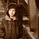 Постер, плакат: Retro black and white photo of sepia Boy homeless bum on street