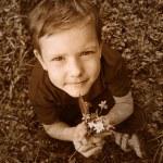 Retro black and white photo of sepia Boy sitting on green grass — Stock Photo #23718749