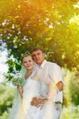 Sunlight bride groom newlyweds blonde standing in a green forest — Stock Photo