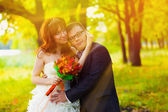 Sunlight bride and groom standing in a green forest in summer at — Stock Photo