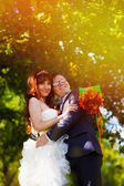 Sunlight Redhead bride and groom with glasses in a green forest — Stock Photo