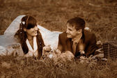Retro black and white photo of sepia bride and groom at a picnic — Stock Photo