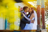 Sunlight Bride and groom standing at old wooden house and kiss — Stock Photo