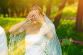 Sunlight bride woman has closed eyes with his hands for a surpri — Stock Photo