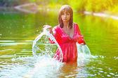 Sunlight brunette woman red dress is wet to waist in splash wate — Stock Photo