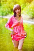 Zonlicht brunette vrouw in rode jurk nat aan de taille in de wat — Stockfoto
