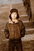 Retro black and white photo of sepia Boy homeless bum in brown j — Stock Photo