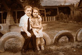 Retro black and white photo of sepia boy and girl children sitti — Stock Photo