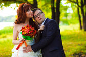 Newlyweds at wedding bride and groom are embracing the green woo — Stock Photo