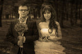 Retro sepia black and white photo bride and groom standing on a — Stock Photo
