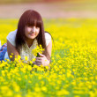 Sunlight beautiful brunette girl lying in a field of yellow flow — Stock Photo